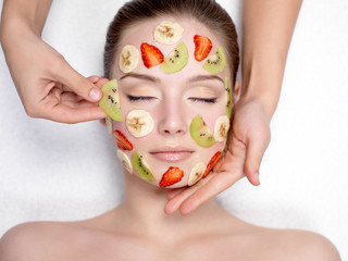 Cosmetician doing fruit mask on a face of  woman
