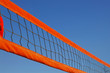 Beach volleyball net against a clear blue sky