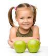 Little girl with two green apples