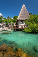 Idyllic mexican jungle scenery with hut on the water
