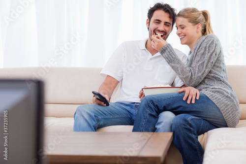 Lovely couple watching TV while eating popcorn
