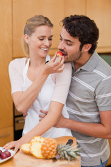 Portrait of a charming couple eating fruits