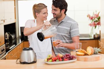 Young couple making fresh fruits juice