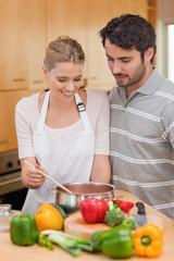 Portrait of a couple preparing a sauce