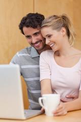 Portrait of a couple using a laptop while having tea