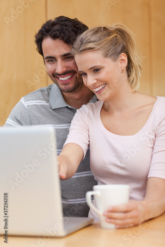 Portrait of a couple using a notebook while having tea