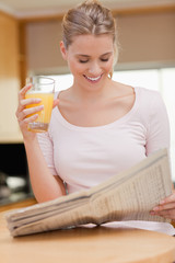 Portrait of a woman reading the news while drinking orange juice
