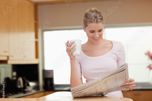Woman reading the news while having tea