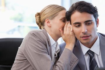 Businesswoman whispering something to her colleague
