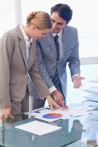 Portrait of smiling business people looking at statistics