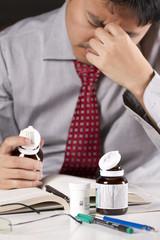 a stress businessman hold a bottle of pill act headache.