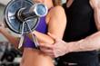 Fitness - Paar trainiert mit Langhantel im Fitnessstudio