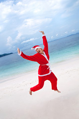 Young woman on the beach in santa's costume