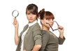 Two serious girls standing with magnifying glass