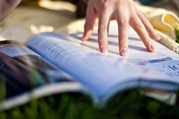 main de jeune femme lisant un magazine au soleil en été
