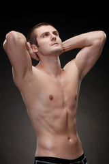 Young muscular man showing his muscles