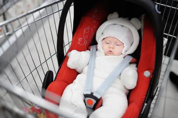 Newborn girl in car seat in a shopping cart