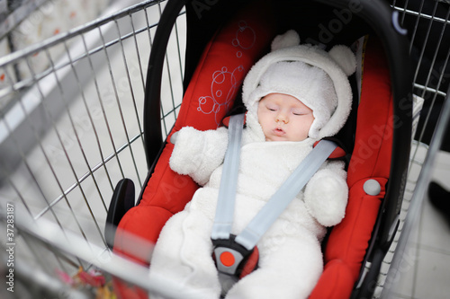 Newborn girl in car seat in a shopping cart