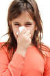 Sick girl sneezing on a tissue isolated on white