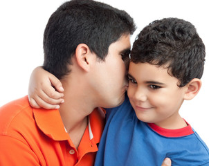 Latin father kissing his beautiful son isolated on white
