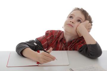 enfant garçon rêvant sur ses devoirs