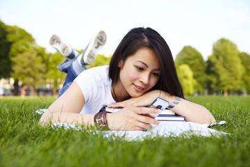 Mädchen tippt SMS, liegen