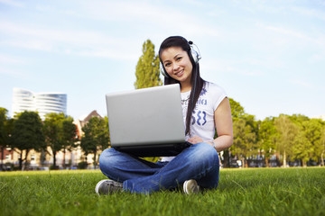 Mädchen mit Laotop, musik hören, sitzen