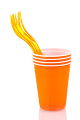Bright orange plastic cups and forks isolated on white
