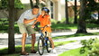 Young Ethnic Father Encouraging Son on Bicycle