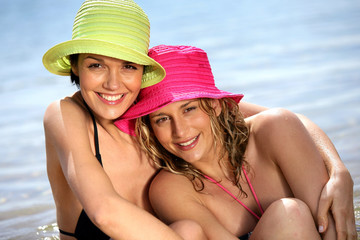 Two friends wearing hats and bikinis at the beach