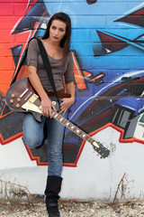 A female guitarist standing before a graffiti.