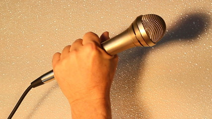 Vocalist singing with a chrome microphone closeup