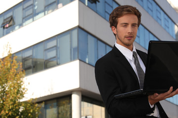 young executive in front of building