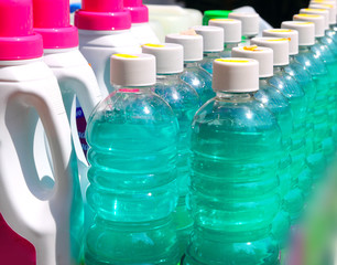 cleaning domestic chemical bottles in a row