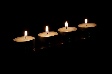 Four burning candles on a black background