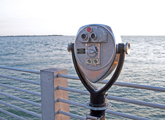 Public beach binoculars on a dock at sunset, Florida.