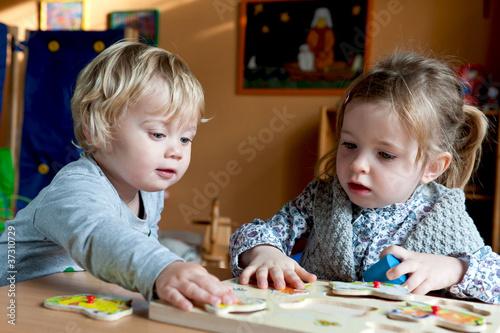 Leinwanddruck Bild Kinder spielen mit Puzzle