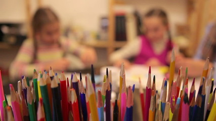 Two girls draw with colored pencils in the paint studio.