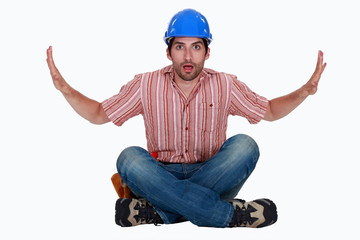 Astonished tradesman pushing against invisible walls