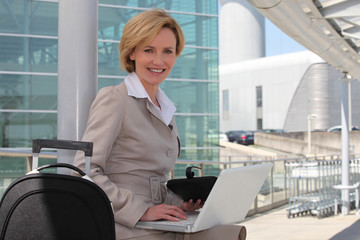 Businesswoman smiling on laptop outside airport