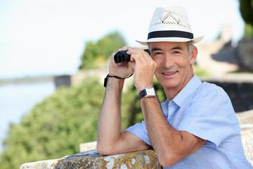 senior gentleman admiring view with binoculars