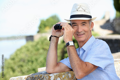 senior gentleman admiring view with binoculars