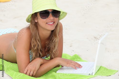 Girl laying on beach with laptop