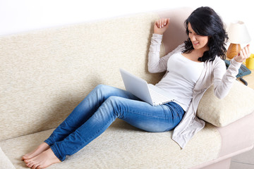 Beautiful woman with netbook laying on sofa
