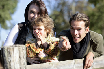 Family leaning against wooden fence