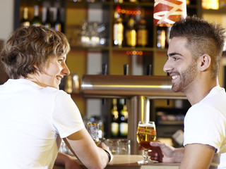Two friends sitting at the bar and talking