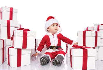 Baby boy in Santa Claus costume sitting between gift boxes