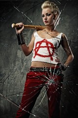 Punk girl with a bat behind broken glass