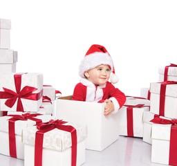 Baby boy in Santa Claus costume sitting inside gift box
