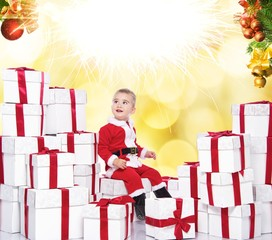 Baby boy in Santa costume on an abstract background